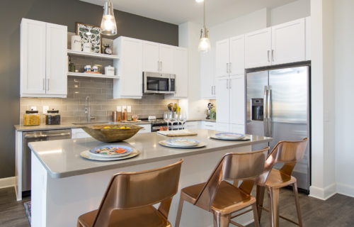 Stylish kitchens with chef-inspired islands and decorative lighting at Alexan on 8th Luxury Apartment Community
